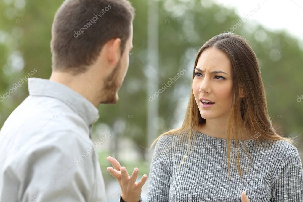 Couple talking seriously outdoors